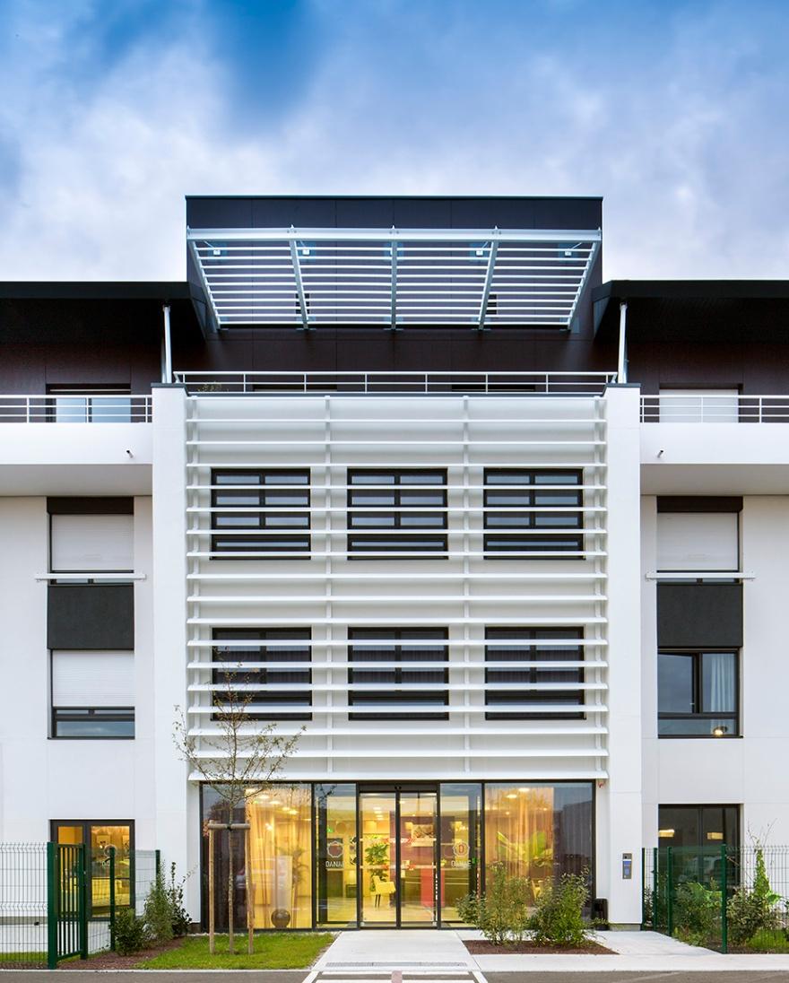 Danae par l'agence d'Architecture de Bordeaux Hubert Saladin Architectes . Vue vers l'entrée de la résidence séniors. Bâtiment en béton peint en marron et blanc. L'entrée est pourvu de brise soleil permettant de tempérer l'intérieur de la maison et des locaux.